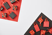 top view of decorative gift boxes and shopping bags on red, white and black background with copy space