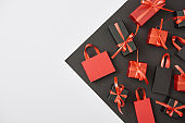 top view of decorative gift boxes and shopping bags on white, black background with copy space