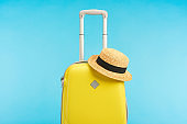 yellow travel bag with straw hat isolated on blue
