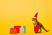 Toy dinosaur in santa hat with shopping bags on yellow background