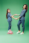 adorable daughter in roller blades holding hands with mother on green background