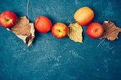 Autumn harvest background with red apples and fall leaves over blackboard.