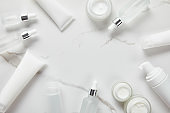 top view of cosmetic glass bottles, jar with cream, moisturizer tubes, dispenser and jasmine on white surface