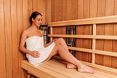 smiling woman in towel with flower in hair in sauna