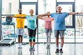 multiethnic senior athletes synchronous doing exercise at sports hall