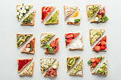 top view of delicious toasts with fruits and vegetables isolated on white