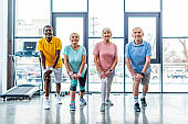 cheerful senior multiethnic sportspeople synchronous stretching at gym