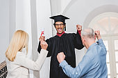 back view of parents gesturing near happy son in graduation cap holding diploma