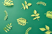 pattern of exotic paper cut palm leaves on green background with copy space