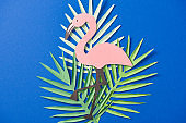 top view of green paper cut exotic leaves and flamingo on blue background