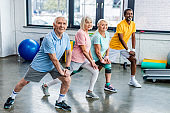 smiling senior multiethnic sportspeople synchronous stretching at sports hall