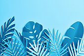 top view of blue exotic paper cut palm leaves on blue background with copy space