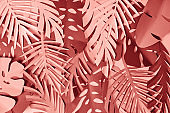 top view of colorful paper cut pink and burgundy palm leaves