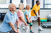 selective focus of senior multiethnic sportspeople synchronous stretching at sports hall