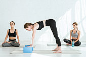 three young women practicing yoga in lotus and puppy dog poses