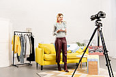 full length view of smiling blogger holding cup of coffee in front of video camera at home
