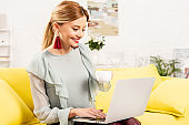 smiling freelancer sitting on yellow sofa with cup of coffee and using laptop