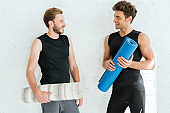 two young smiling men talking while holding yoga mats