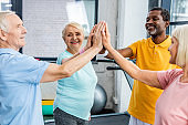 smiling multicultural senior athletes stacking hands together at gym
