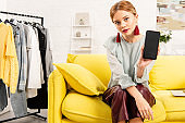 charming girl in trendy earrings sitting on yellow sofa and using smartphone at home