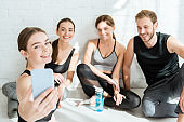 cheerful girl taking selfie on smartphone with friends sitting in easy poses