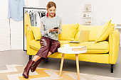 charming freelancer in trendy earrings sitting on yellow sofa and using smartphone at home