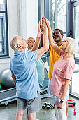 smiling senior multicultural sportspeople putting hands together at gym