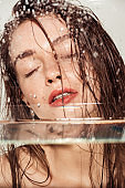 selective focus of beautiful young woman with coral lips posing through glass with water drops isolated on grey