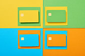 top view of empty credit cards on green, orange, blue and yellow background