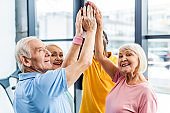 senior happy multicultural sportspeople putting hands together at gym