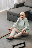 lonely senior woman with blonde hair sitting on floor with walking cane near sofa