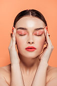 beautiful trendy young woman with glitter makeup and eyes closed touching face isolated on coral