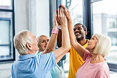 selective focus of happy senior multicultural sportspeople putting hands together at gym
