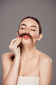 beautiful girl pouting lips and holding hair as moustache isolated on grey
