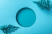 blue fern leaves near round hole on blue paper