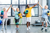 laughing senior multiethnic athletes with fitness mats taking high fives to each other at gym