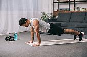 bi-racial man doing push ups in sportswear on  fitness mat