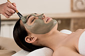 cropped view of beautician applying clay mask on woman face