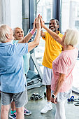senior multicultural sportspeople putting hands together at gym