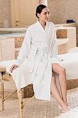 attractive asian woman in bathrobe sitting on massage table at spa