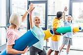 smiling senior multiethnic sportspeople with fitness mats taking high fives to each other at gym