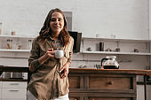 Beautiful girl holding coffee cup and smiling at camera on kitchen