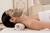 side view of attractive woman lying with clay mask on face at spa