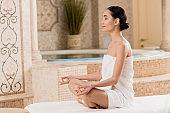 beautiful asian woman in towel meditating in lotus pose at spa