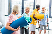 senior sportswomen holding fitness mats and their male friends standing behind at gym