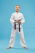 Portrait of girl in white kimono with blue belt in studio.