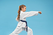 Karate girl standing in stance, practicing punching.
