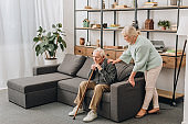 retired wife standing near sad senior husband sitting with walking cane on sofa