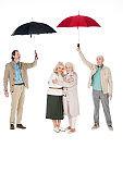 senior men holding umbrellas near women standing and hugging isolated on white