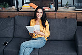 Smiling woman in yellow shirt sitting on sofa with digital tablet and smartphone with blank screen